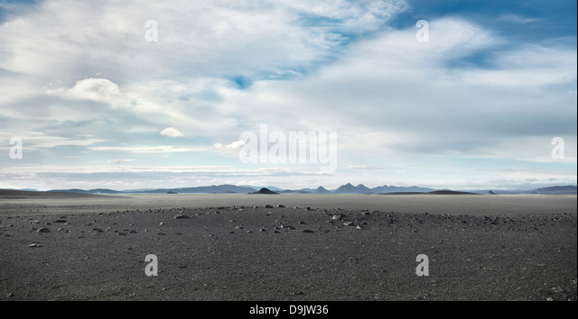 Grey barren landscape under cloudy sky - Stock Image