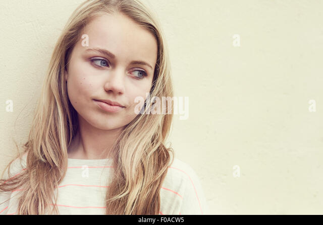 Portrait of girl with long blond hair in front of wall - Stock Image