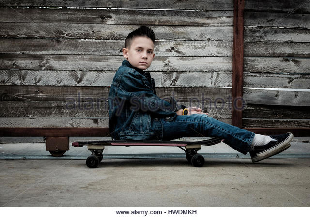 Boy sitting on skateboard - Stock-Bilder