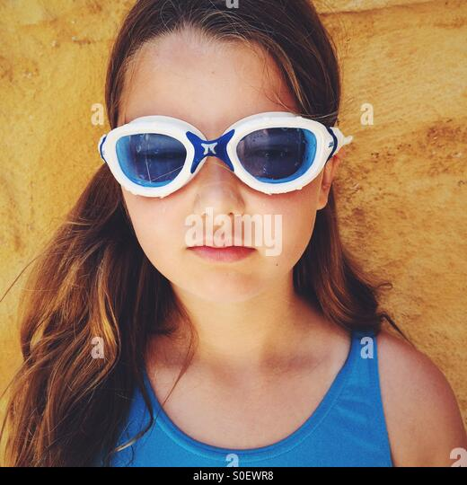 Girl, wearing swimming goggle and a blue swimsuit. - Stock Image