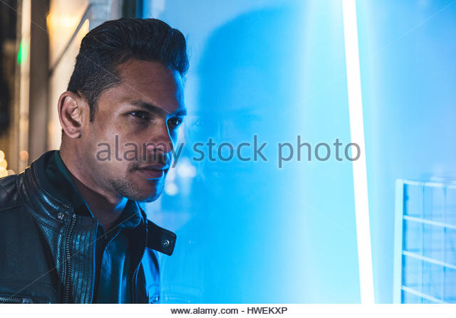 Portrait of mid adult man in city at night, standing next to illuminated window, Lisbon, Portugal - Stock-Bilder
