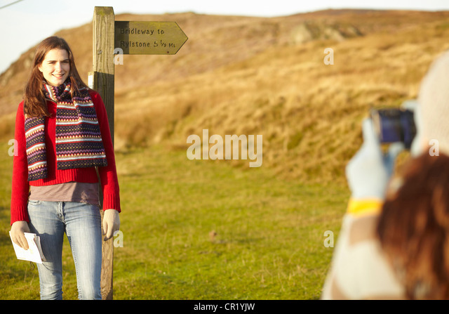 Woman taking picture of friend at post - Stock Image