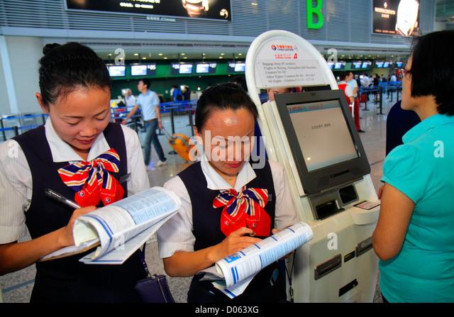 China Shanghai Changning District Hongqiao Airport Terminal 2 SHA self-service check-in kiosk Asian woman uniform - Stock Image