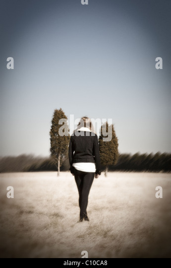A teenage girl stand in a field wearing black tights and a black coat with two trees in the distance. - Stock-Bilder