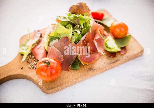 Ham and salad on chopping board, close-up - Stock Image