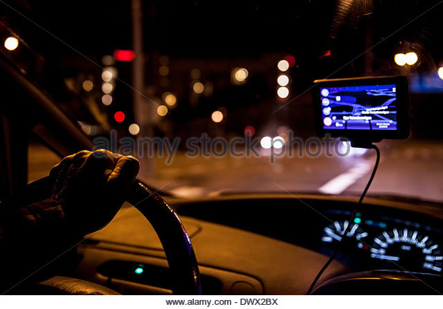 Cropped image of man driving car at night - Stock Image