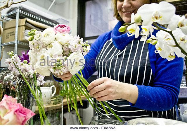 Floral designer preparing flowers in studio - Stock Image