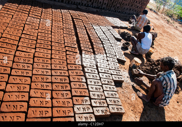 Indian men making house bricks buy hand using a mould and wet clay / mud in the rural Indian countryside. Andhra - Stock-Bilder