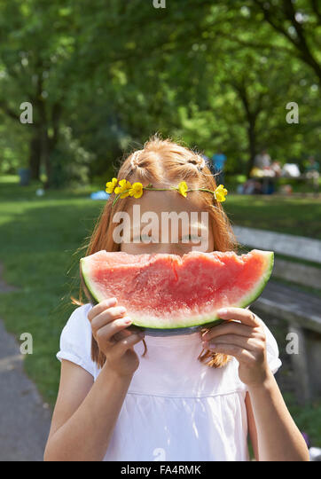 Portrait of a girl enjoying slice of watermelon at picnic, Munich, Bavaria, Germany - Stock Image