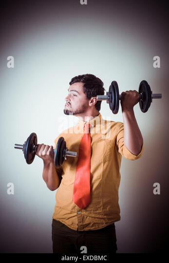 funny crazy young man weightlifting on gray background - Stock Image