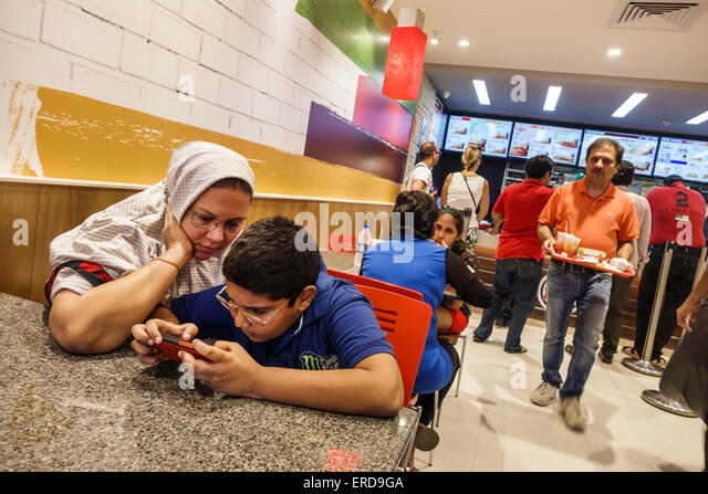 India Asian Mumbai Lower Parel High Street Phoenix mall inside restaurant Burger King fast food boy son woman mother - Stock Image