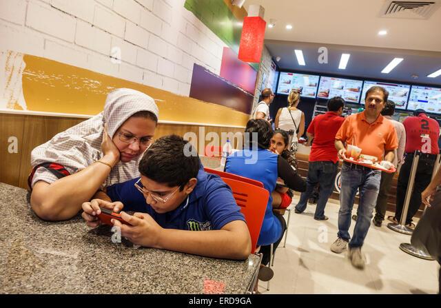 Mumbai India Asian Lower Parel High Street Phoenix mall inside restaurant Burger King fast food boy son woman mother - Stock Image