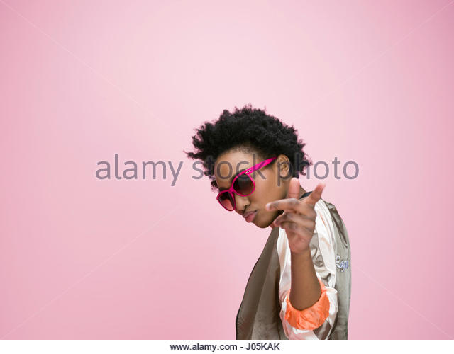 Portrait cool African American young woman gesturing against pink background - Stock Image