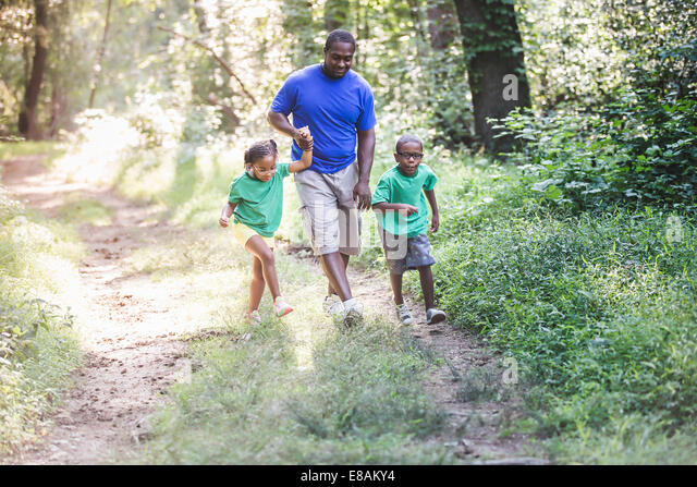 Father walking through forest with daughter and son at eco camp - Stock-Bilder