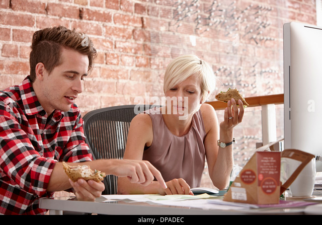 Two colleagues eating sandwiches at desk - Stock Image