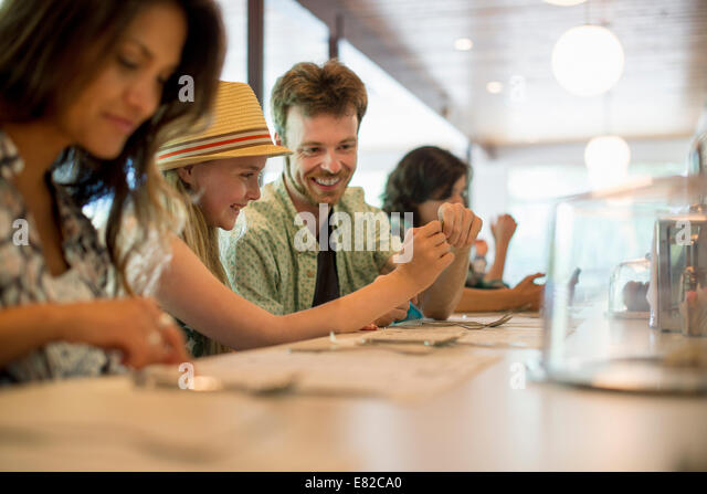 A group of friends sitting at the bar in a diner. Checking their phones. - Stock Image