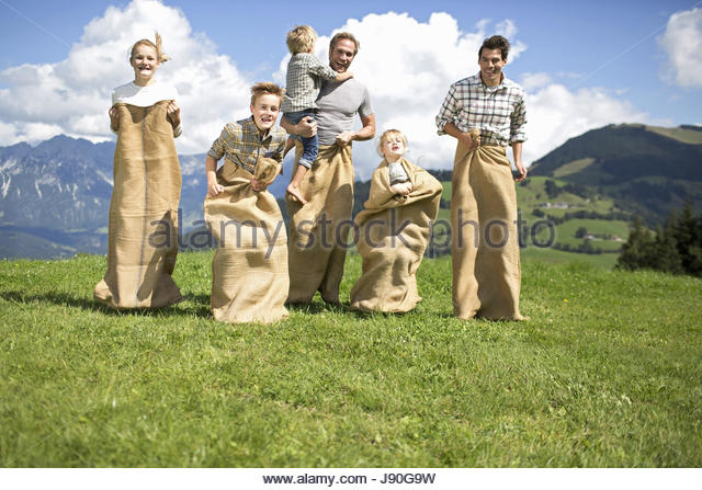 Fathers And Children Having Sack Race In Countryside - Stock-Bilder