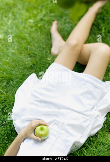 Woman lying in grass, holding apple, low section - Stock Image