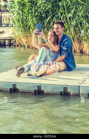 Couple in love sitting on the pier, selfie - Stock Image