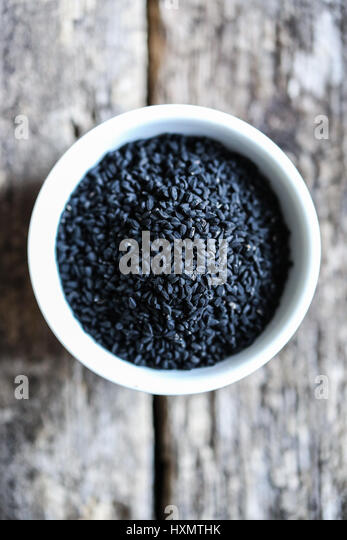 Black cumin seeds in a white bowl on a wooden table - Stock Image
