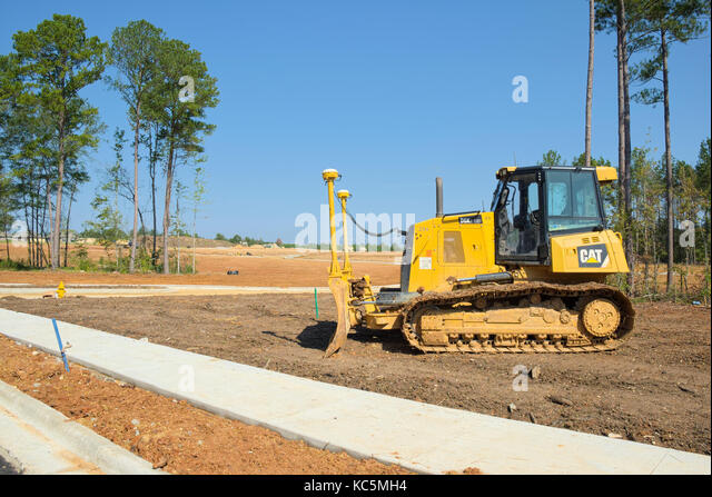 An idle Caterpillar (CAT) D6K2 LGP bulldozer waiting to be used at a housing construction site at the Woodland Creek - Stock Image