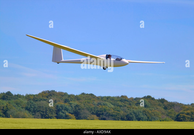 A modern glider just about to land on a grass airfield - Stock Image