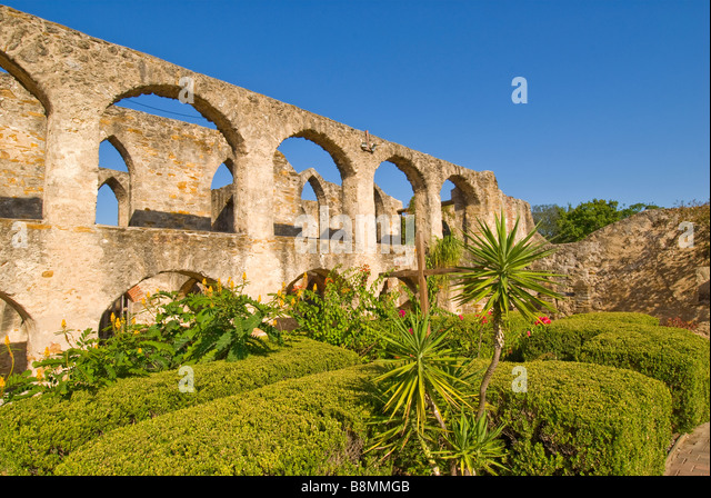 Mission San Jose arched stone walls doorways with green shrubs and spanish bayonets Missions National Park San Antonio - Stock Image