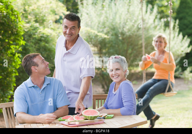 Two mature couples in a lawn - Stock Image