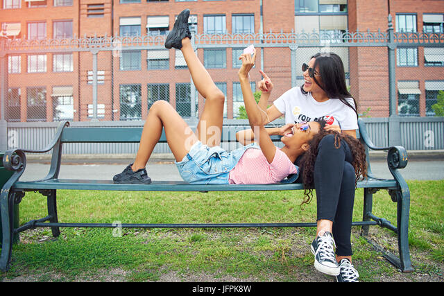 Two smiling young women sharing earphones and making faces while sitting and lying on a city bench taking self portraits - Stock Image