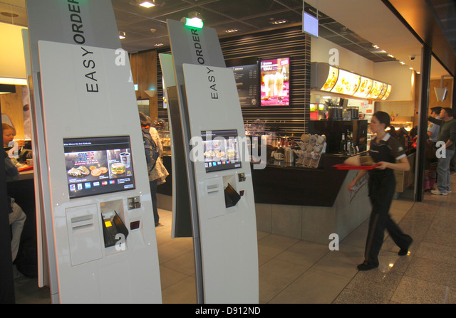 Germany Frankfurt am Main Airport FRA terminal gate area concourse McDonald's fast food restaurant self-service - Stock Image