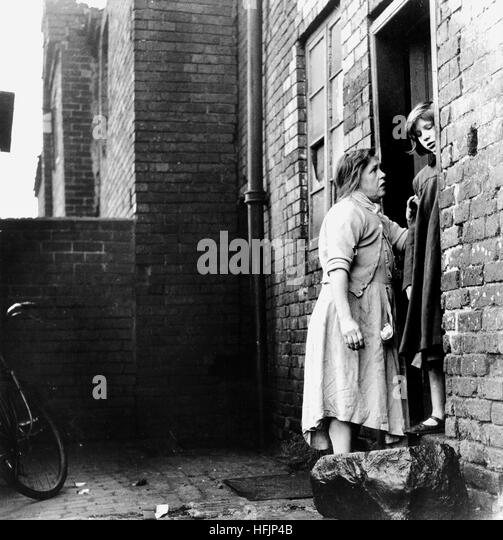 Mother and daughter on the doorstep of slum housing in The Minories, Dudley, West Midlands 1953 - Stock Image
