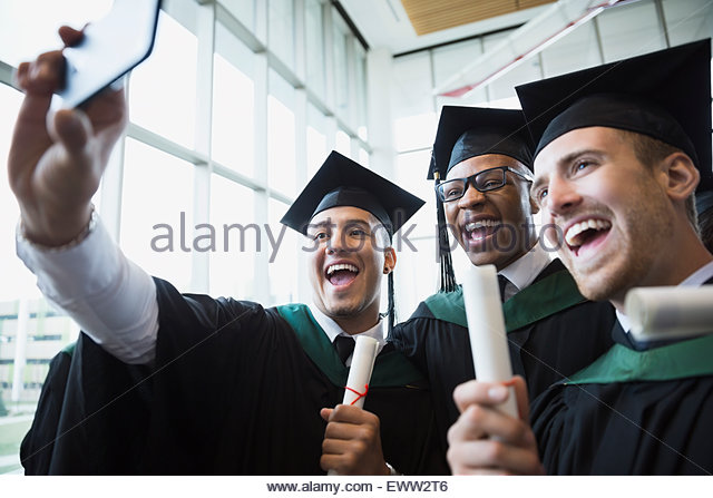 Enthusiastic college graduates cap and gown taking selfie - Stock Image
