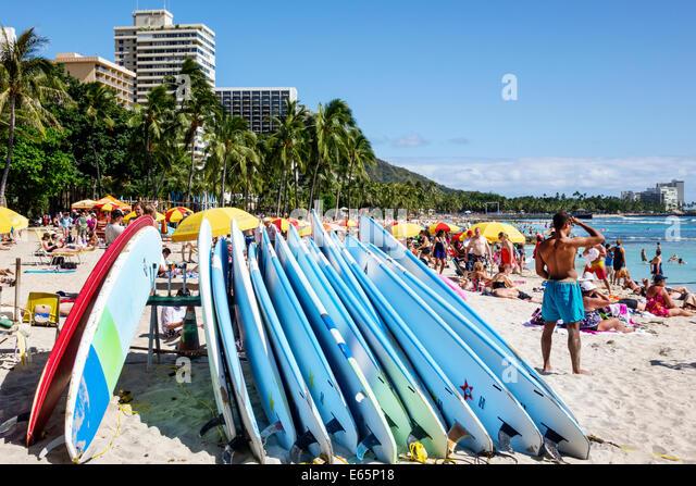 Hawaii Hawaiian Honolulu Waikiki Beach resort Kuhio Beach State Park Pacific Ocean sunbathers families crowded umbrellas - Stock Image