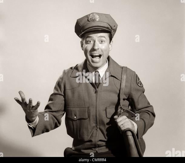 1960s STUDIO PORTRAIT OF HAPPY MAN MAILMAN POSTMAN LOOKING AT CAMERA - Stock Image