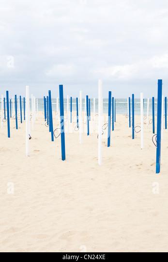 Beach umbrella poles on sandy beach - Stock Image