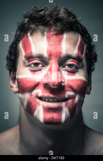 Portrait of smiling man with British flag painted on his face. - Stock Image