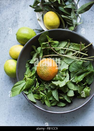 Overhead view of mint leaves and citrus fruits in bowl - Stock Image