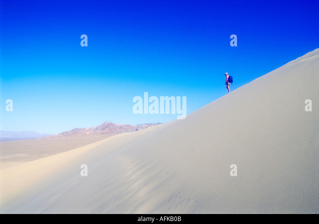 Man hiking on tall sand dune in Death Valley California Model Released Photo - Stock Image