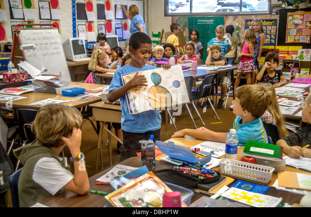 An African American elementary schoolboy uses an illustrated astronomy book to explain the Solar System - Stock Image