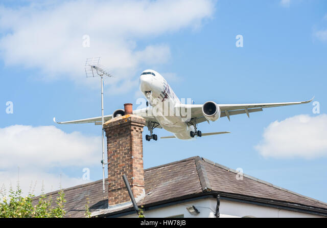 Qatar Airways Airbus A350 on landing approach over rooftops to participate at the Farnborough Airshow,  UK - Stock Image