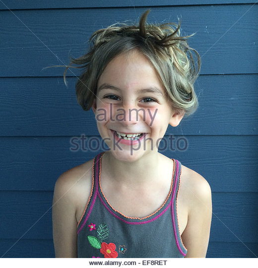 Portrait of smiling girl against blue wall - Stock Image