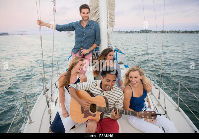 Friends on sailing boat, man playing guitar - Stock Image