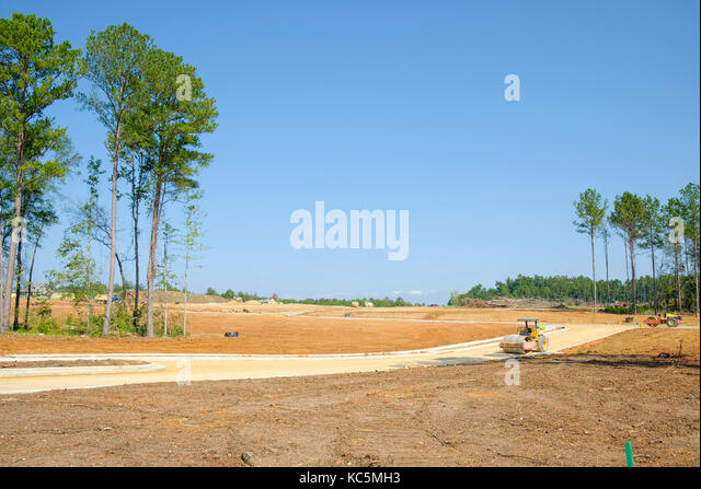Large new residential subdivision construction site work, clearing the land and building roads for new homes in - Stock Image