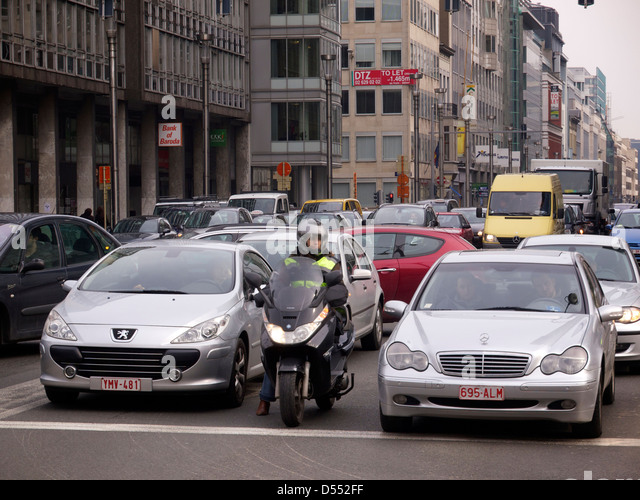 Brussels is one of the most congested cities in Europe and this woman tries to beat the traffic using a motorcycle. - Stock Image