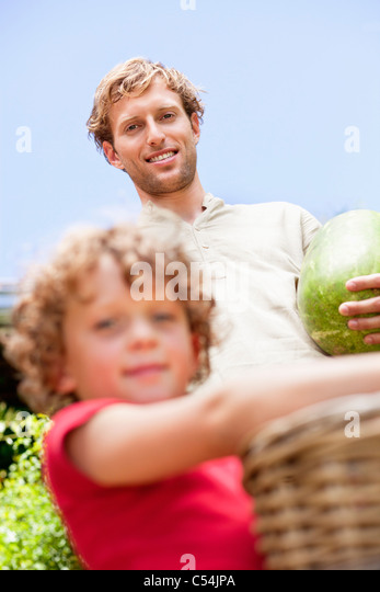 Father and son holding fruits - Stock Image