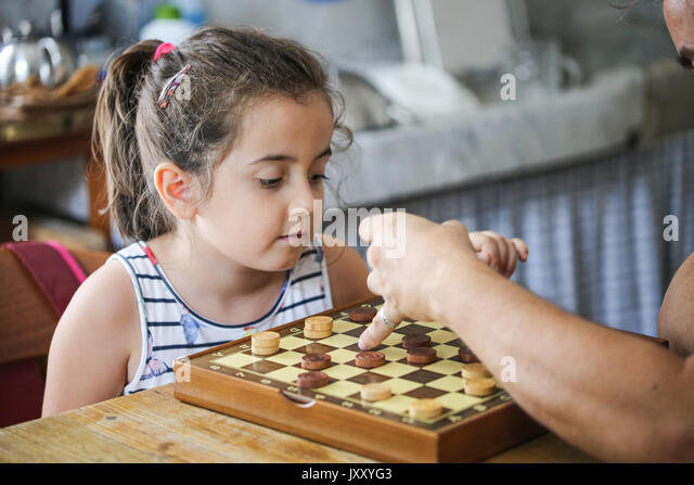 Playing checkers with dad - Stock Image
