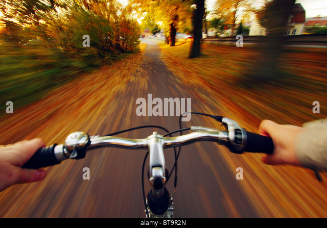 Man speeding with his bicycle down a street full of autumn leaves. - Stock Image