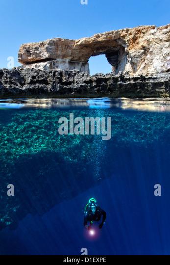 Split shot half and half with diver and rock arch Azure window in the Mediterranean Sea near Gozo, Malta - Stock Image