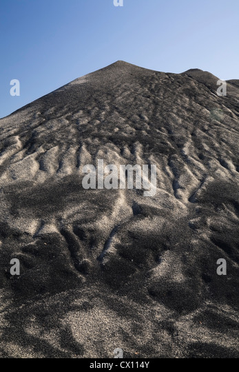 Mound of sand mixed with earth after heavy rain in commercial sand pit - Stock Image