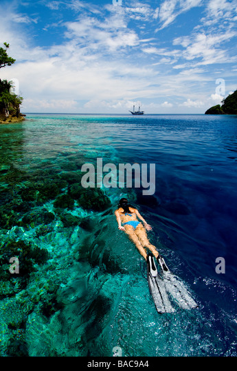 Snorkeling in Raja Empat, Papua, Indonesia, female diver, bikini, clear water, shallow water,  fotosub, great visibility, - Stock Image